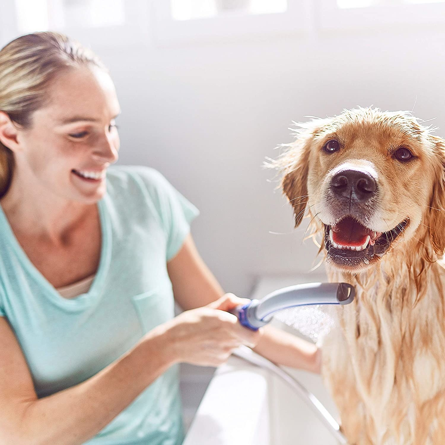 The curved bath wand being used in a bathtub to wet a dog