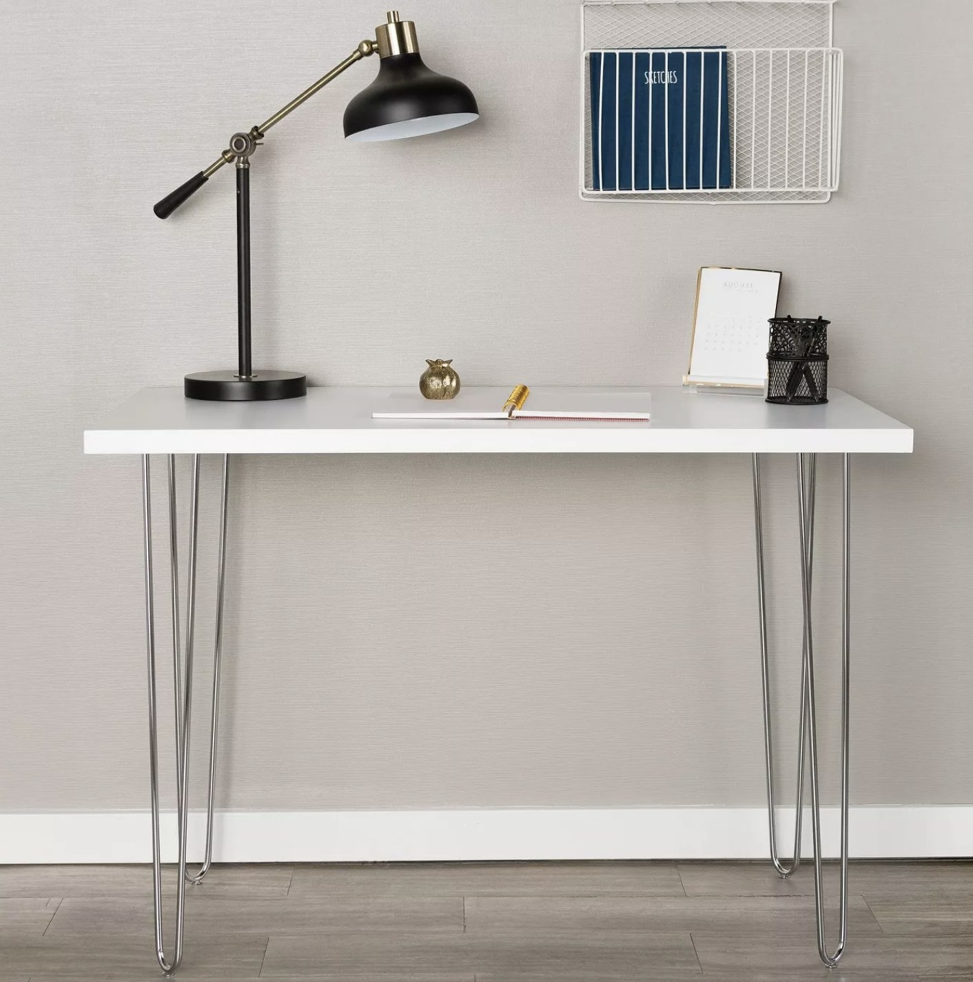 A white writing desk with silver chrome hairpin legs.