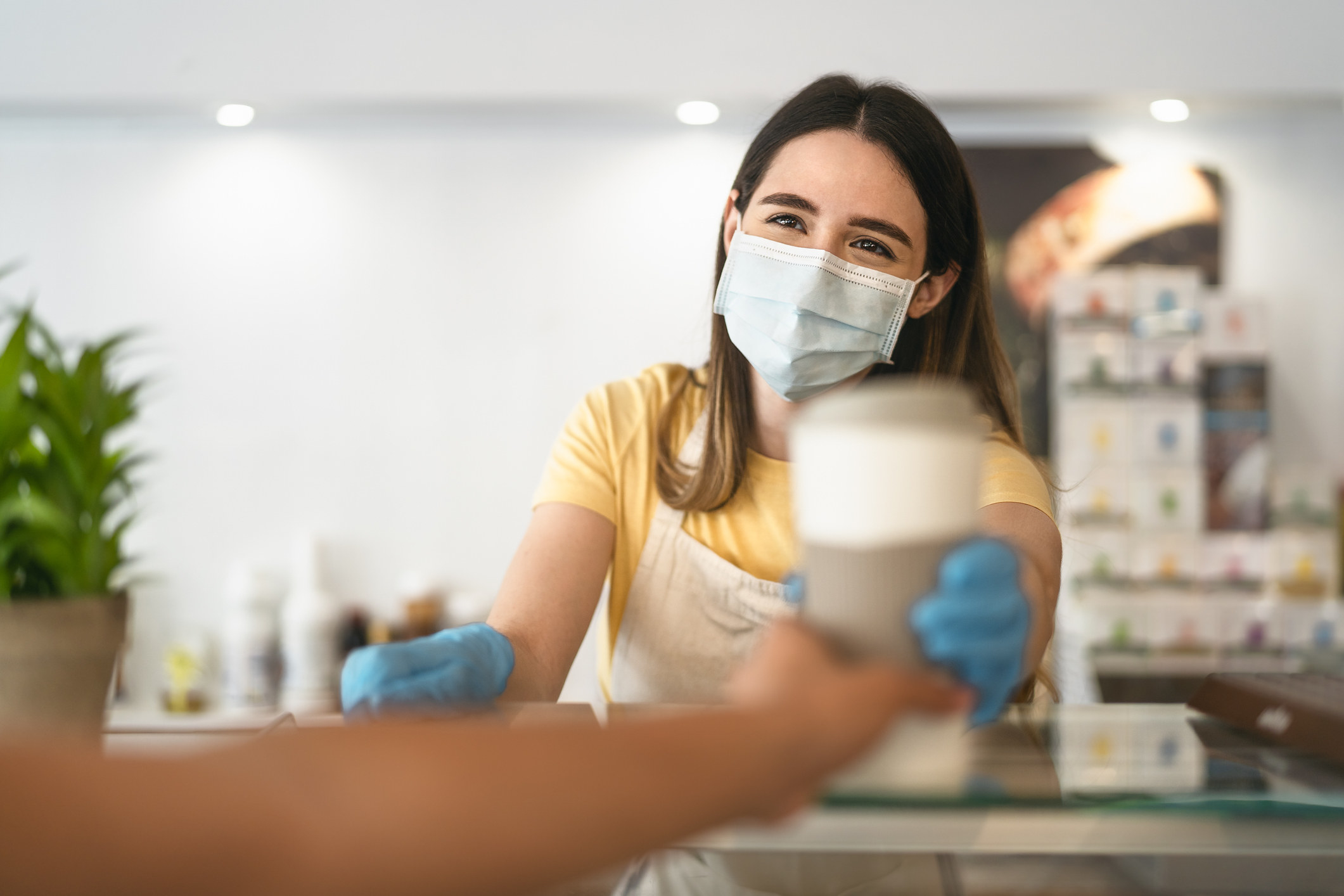barista wearing mask handing cup of coffee to customer