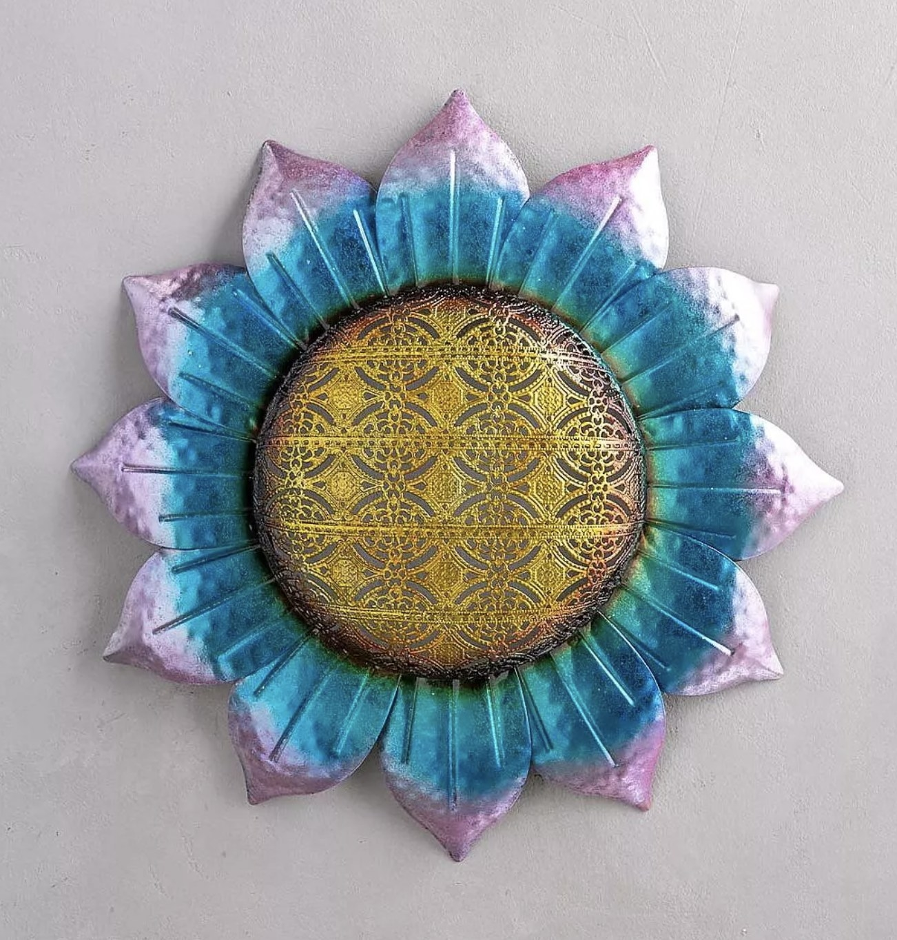 An iridescent 3D flower wall art piece with a lace design in the center