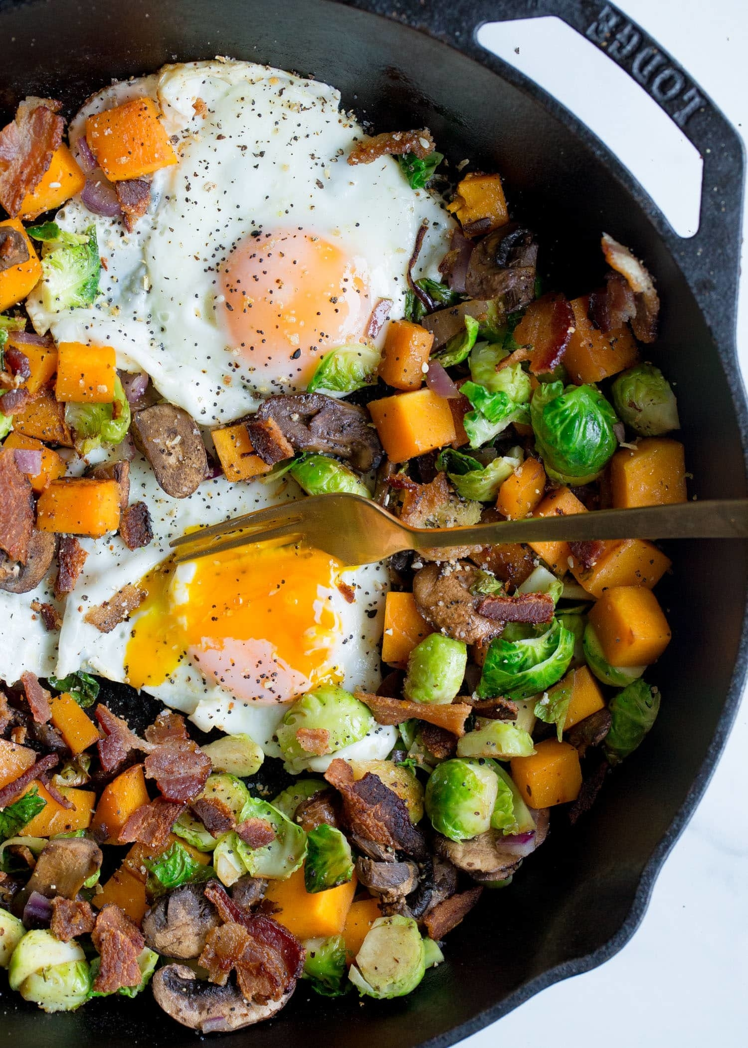 A skillet filled with chopped Brussels sprouts, mushrooms, bacon, and sweet potatoes, and topped with baked eggs.