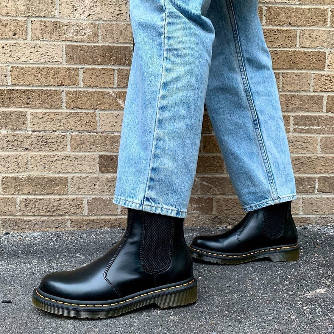 Model wears black Dr. Martens 2976 Chelsea Boots with relaxed mom jeans