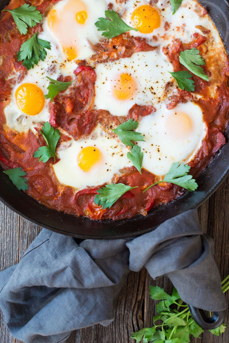 A skillet of bright-red tomato sauce, topped with baked eggs and cilantro.