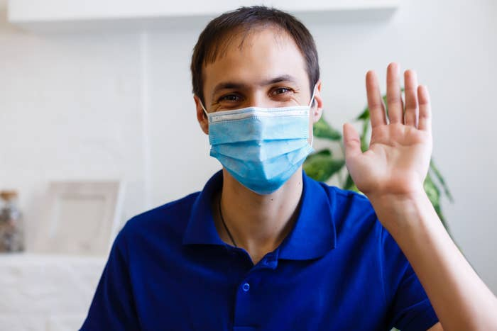 man wearing a mask and waving
