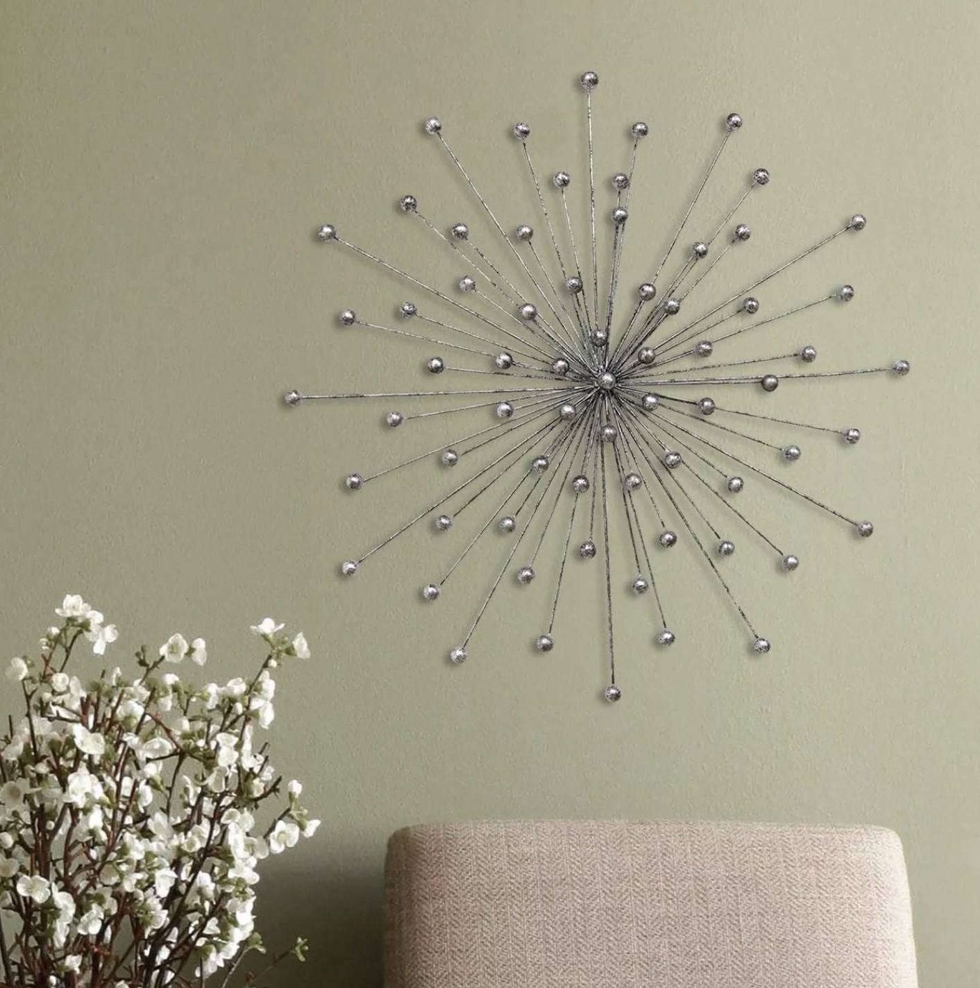 A silver chrome starburst wall decor hanging on a wall