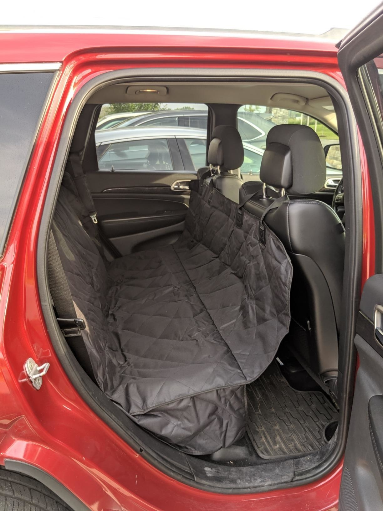 The cover in use in the backseat of a car, anchored to the headrests, creating a hammock that does not allow dog access to floor of car