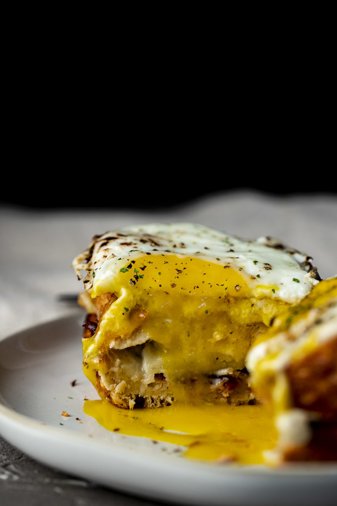 A tall sandwich made with crusty bread, bacon, and cheese, topped with a gooey bechamel sauce and a runny fried egg.