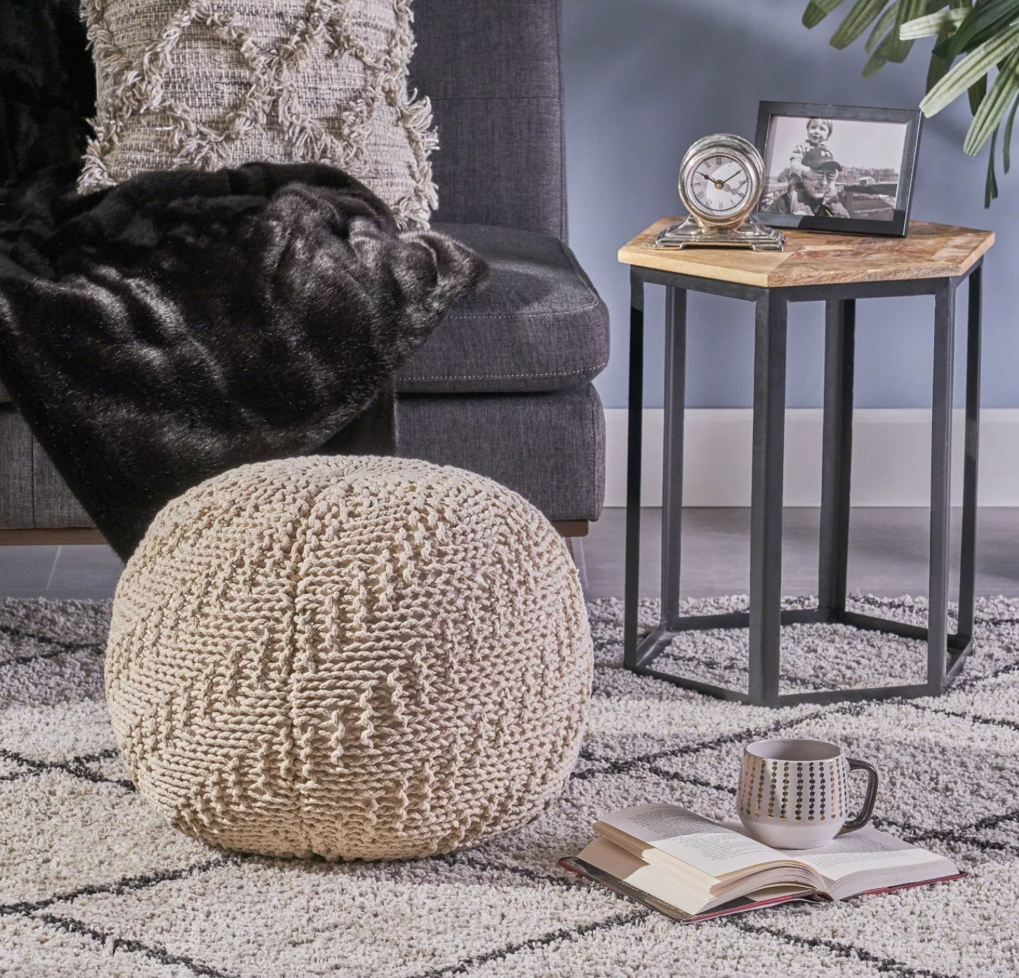 A cream knitted pouf on a rug in a living room