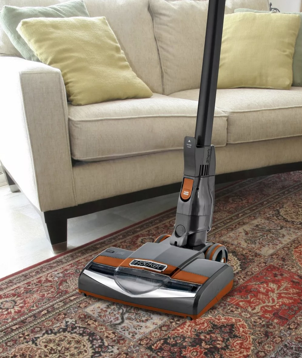An orange and silver corded vacuum on a rug in a living room
