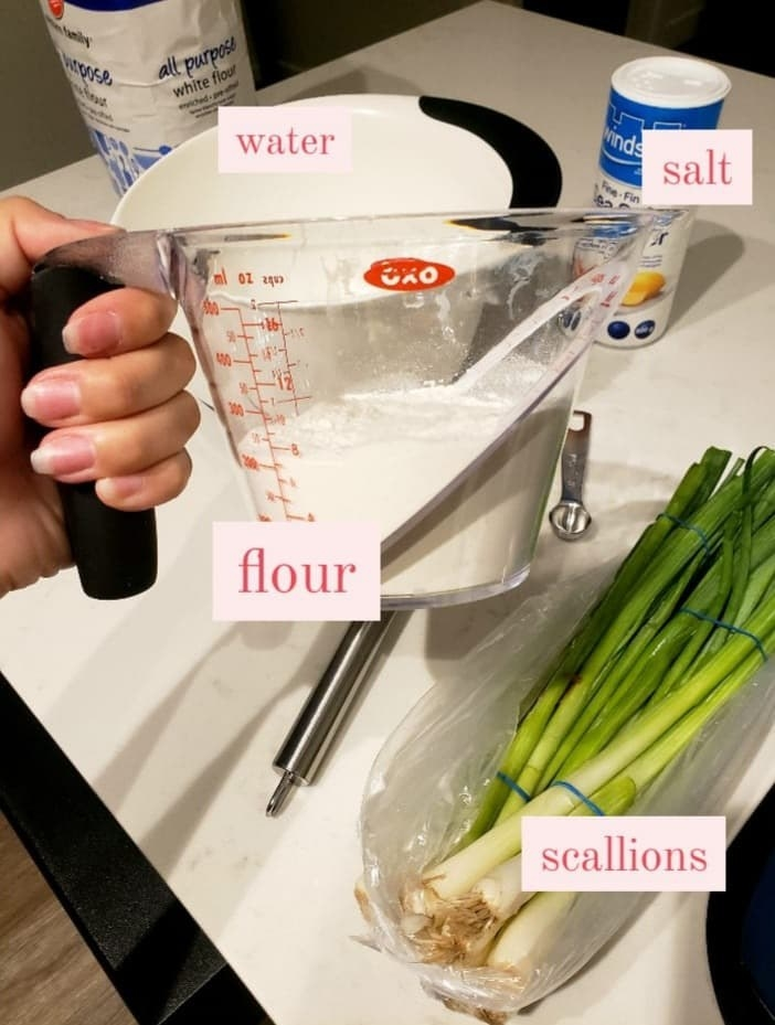 The writer holds a cup of flour over a scallions, salt, a bowl, a bag of flour, and a whisk on the counter
