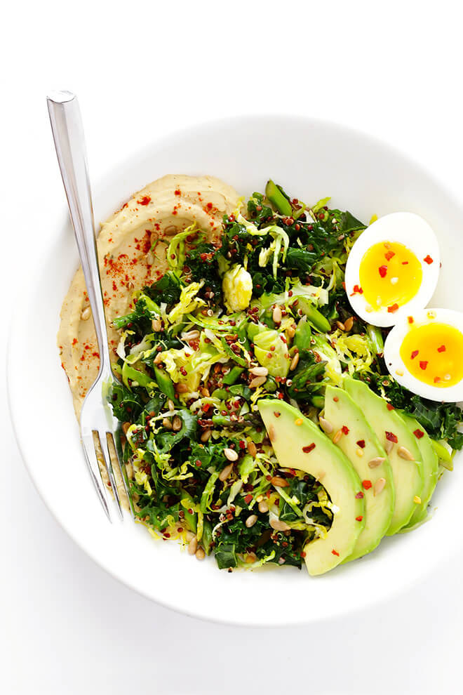 A bowl with hummus smeared across the bottom, topped with a pile of sauteed greens, sliced avocado, and a soft-boiled egg.