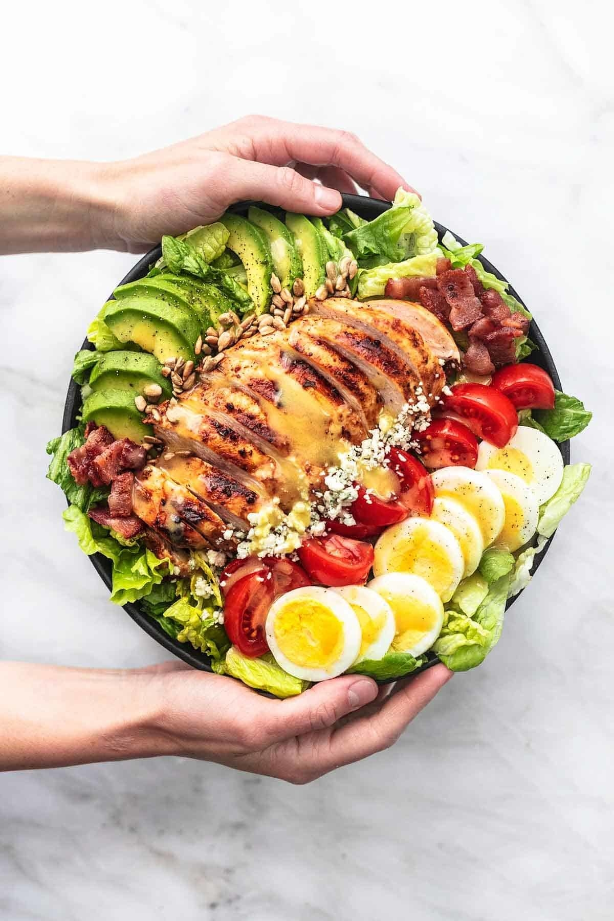A large salad bowl, filled with shredded greens and topped with chicken, sliced tomatoes, sliced eggs, avocado, and corn.