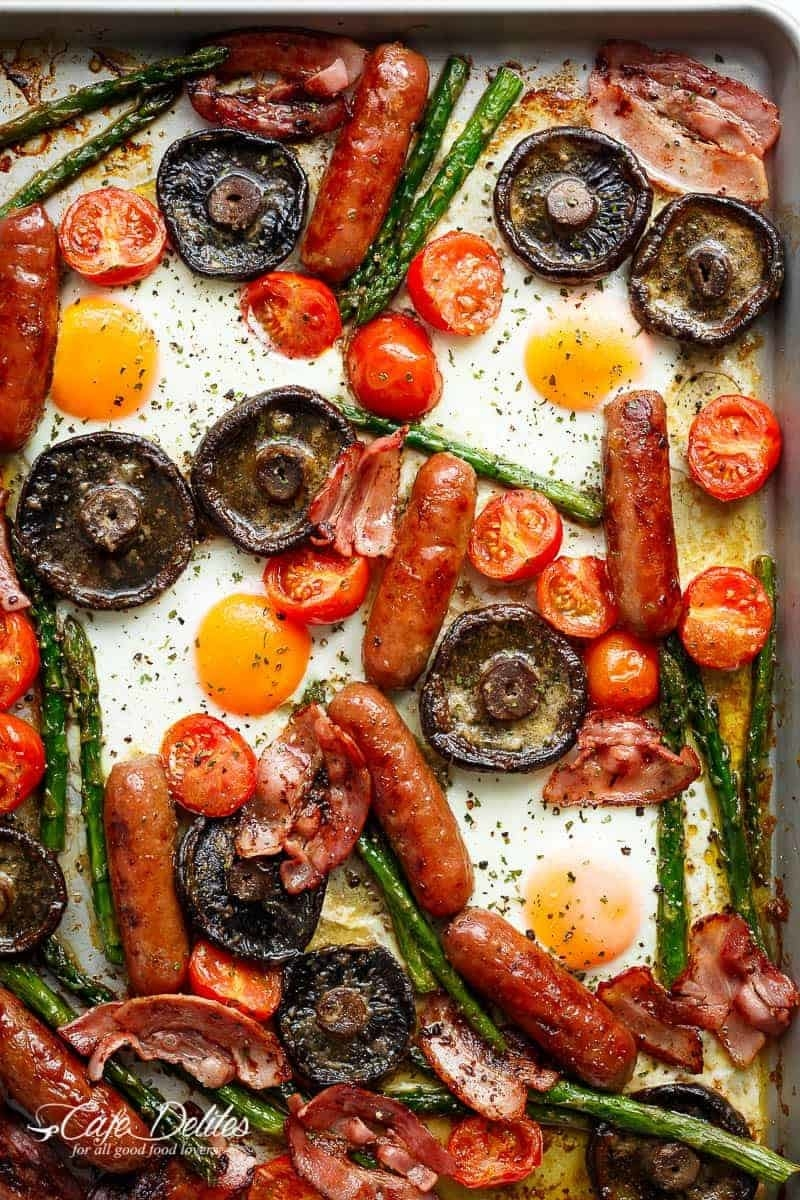 A sheet pan filled with roasted vegetables and meats, with runny baked eggs placed throughout.