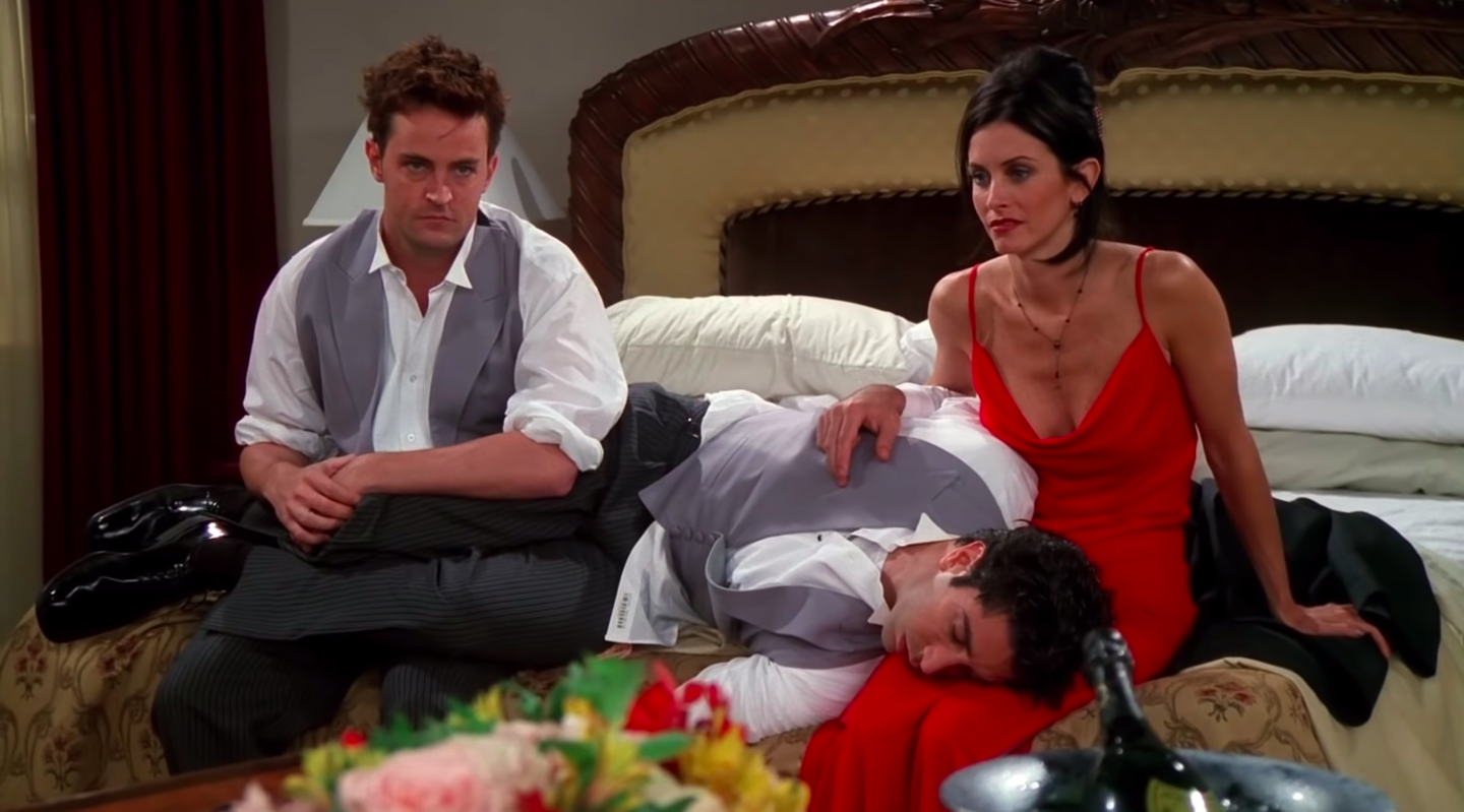 Chandler and Monica, tired and frustrated, sit on a hotel bed while Ross sleeps between them