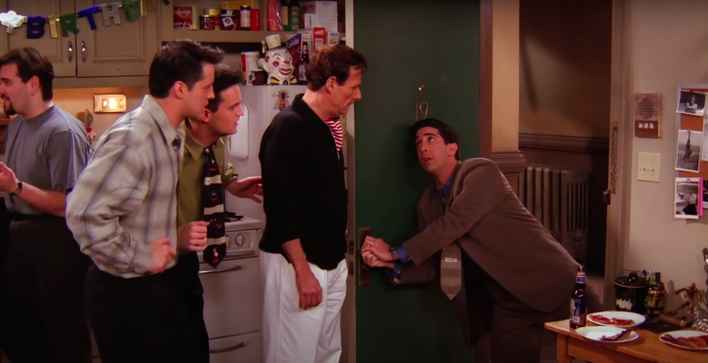 Ross is lunging and holding onto Chandler and Joey's doorknob while Rachel's dad, Chandler and Joey look at him