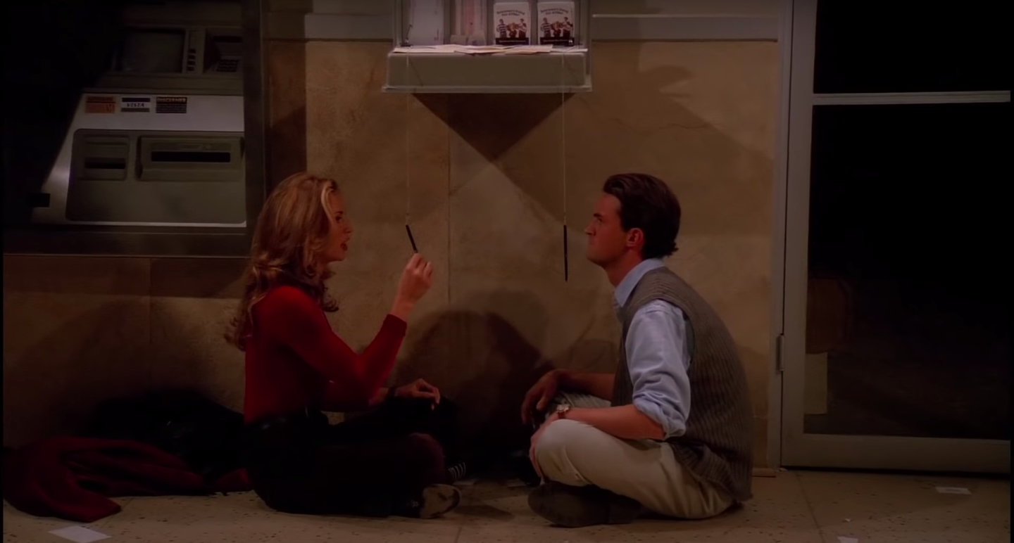Chandler and Jill Goodacre sit on the ATM vestibule floor, playing with the ATM pens