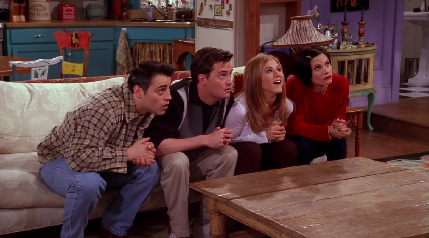 Joey, Chandler, Rachel and Monica sit on the apartment couch, all looking up