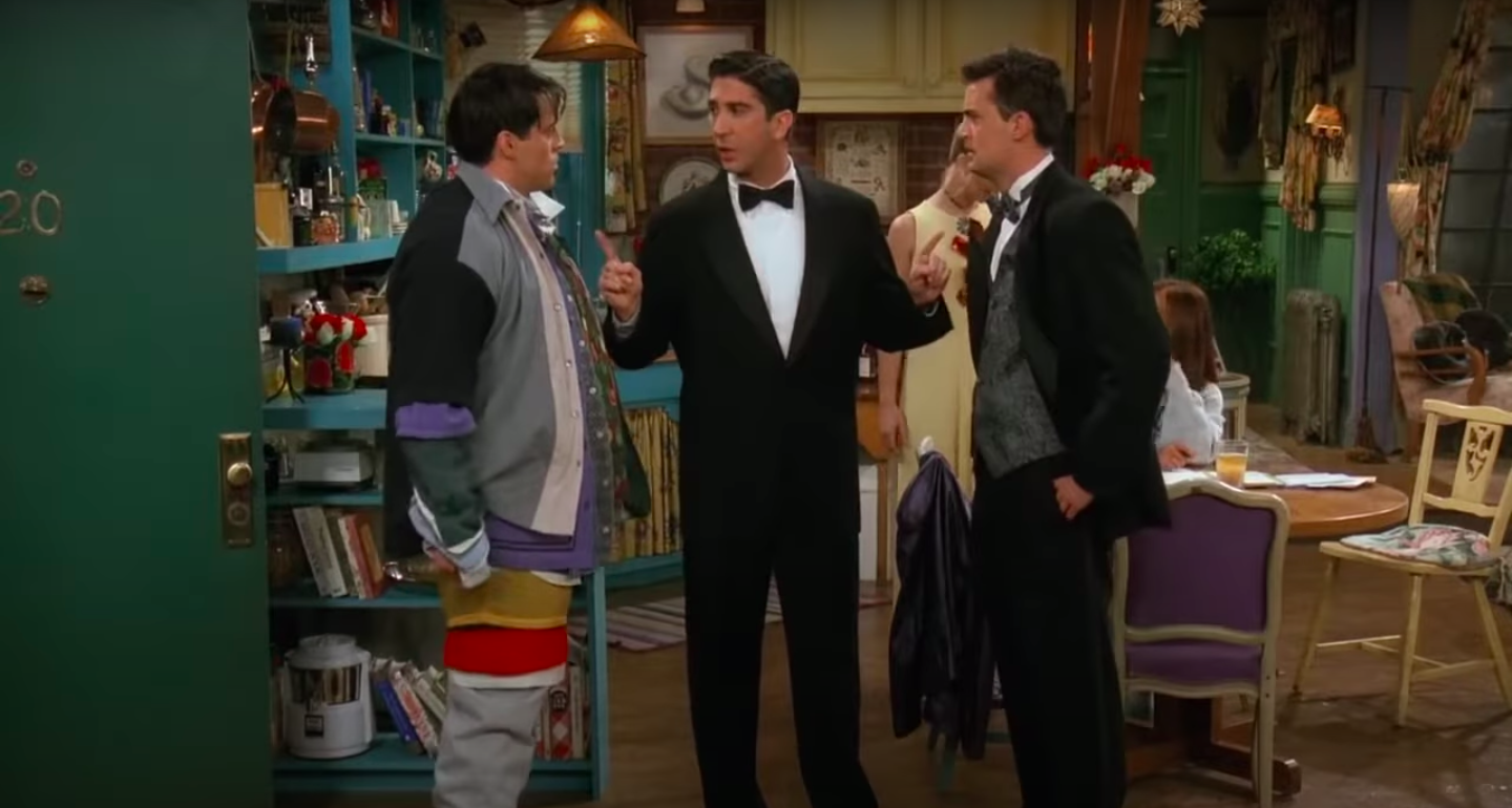 Ross stands between a fighting Chandler and Joey, the latter of whom is wearing all of Chandler's clothes