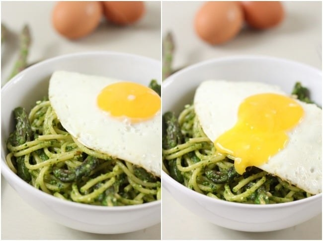 A bowl of bright green spaghetti with asparagus mixed in, topped with a fried egg.