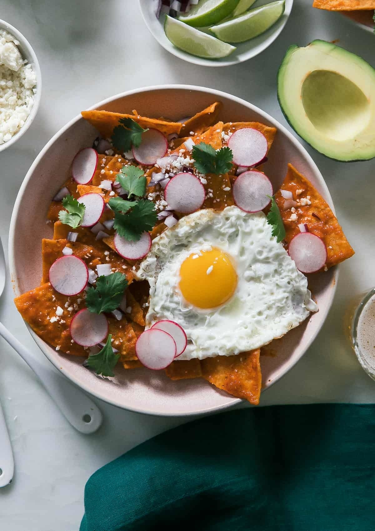 A plate covered in tortilla chips, which were tossed in a tomato sauce, topped with sliced radishes, cilantro, and a fried egg.