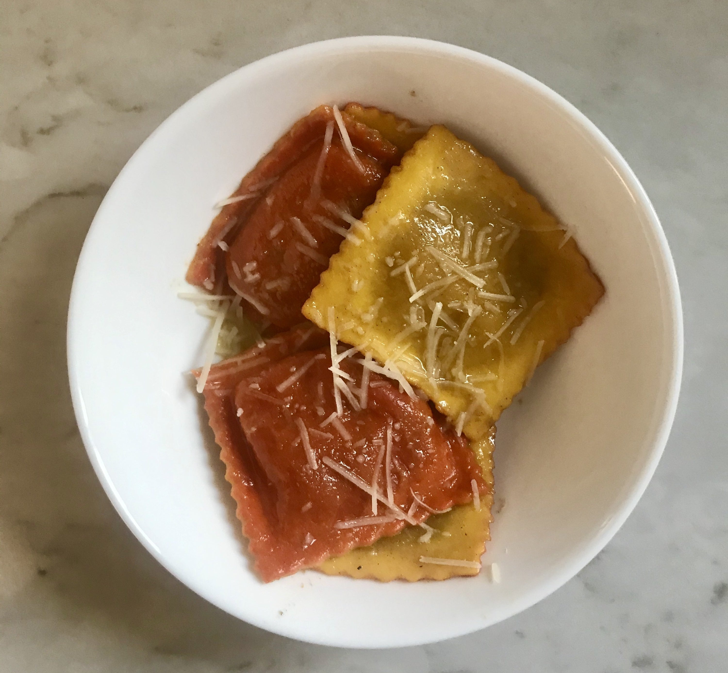 A white bowl filled with orange and yellow raviolis topped with a butter sauce and shreds of parmesan cheese