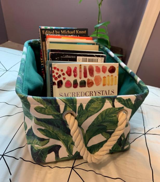Tropical leaf print fabric storage bin with rope handles.