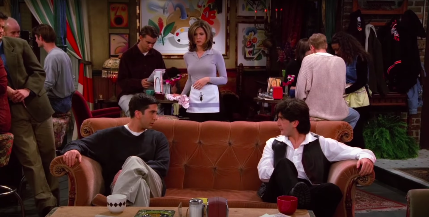 Ross and Russ (both played by David Schwimmer) face each other on the Central Perk couch while Rachel looks on