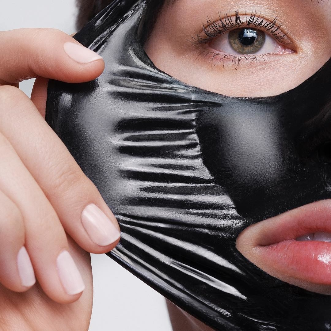 A charcoal mask being peeled in one pull off of someones face