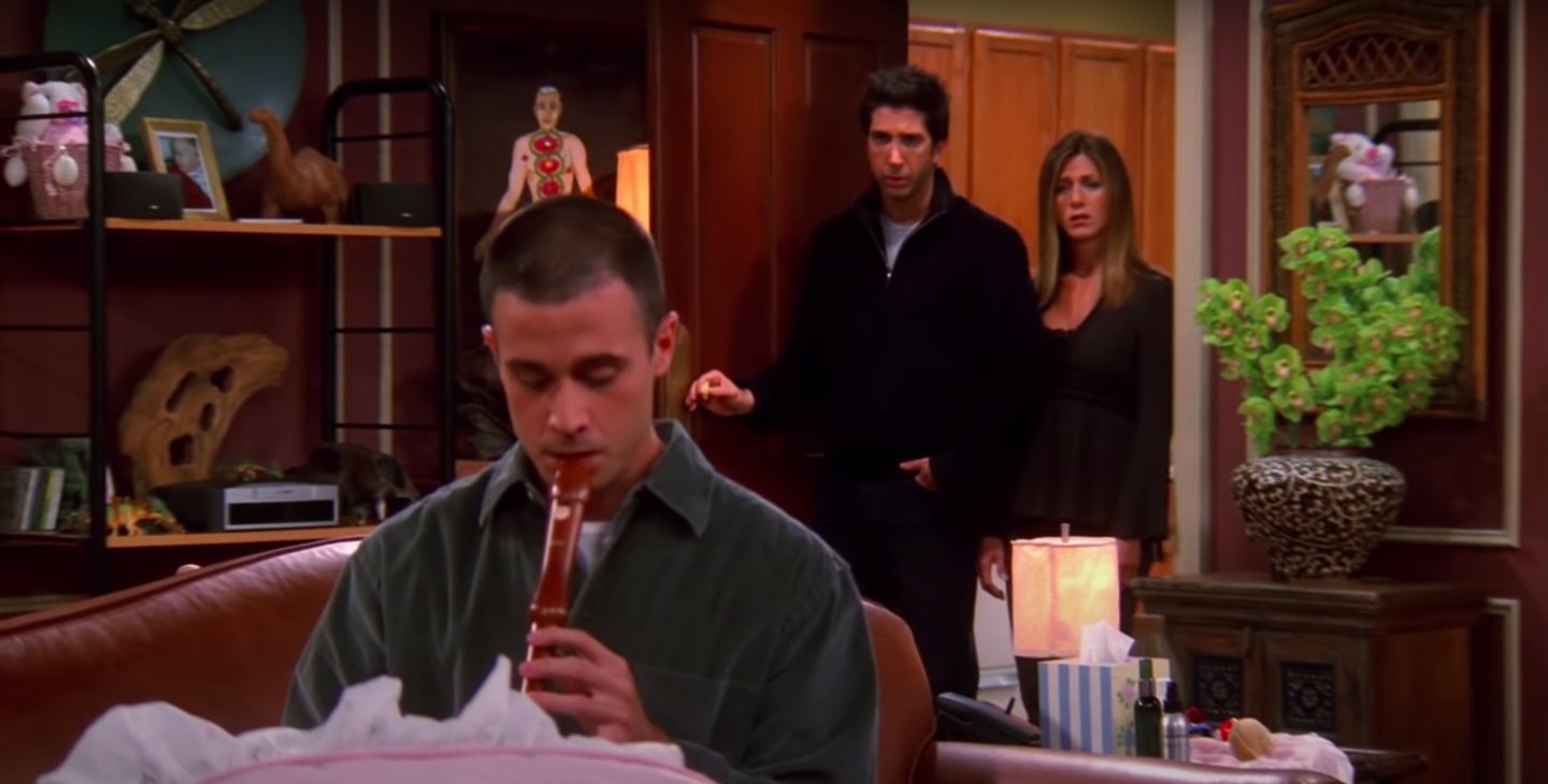 Sandy, the male nanny, plays the recorder for Emma while Rachel and Ross look on