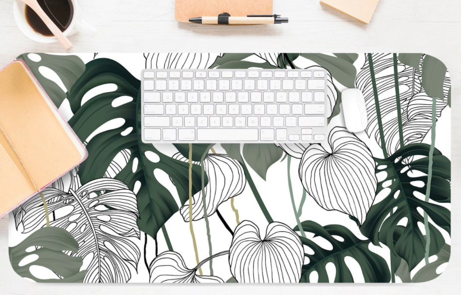 Desk mat featuring plant fronds on a cream background.