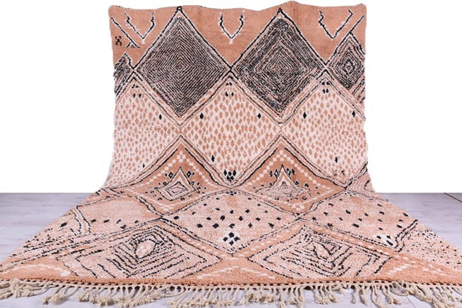 The large rectangular rug with light pink, black, and cream diamonds throughout and dark beige tassels