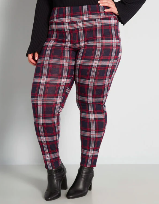 A person wears a pair of plaid leggings with ankle boots