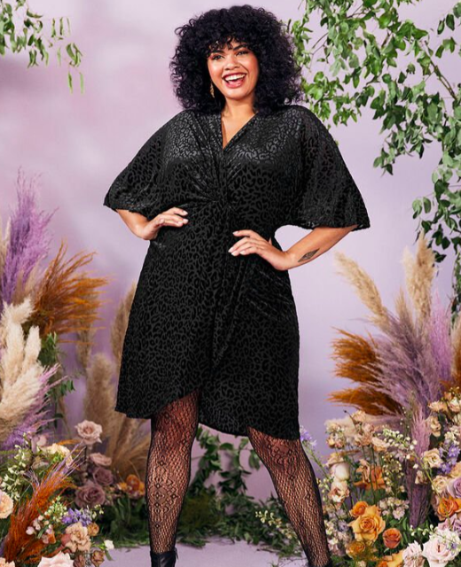A person wears a leopard print dress that's ruched at the waist and a pair of fishnet stockings
