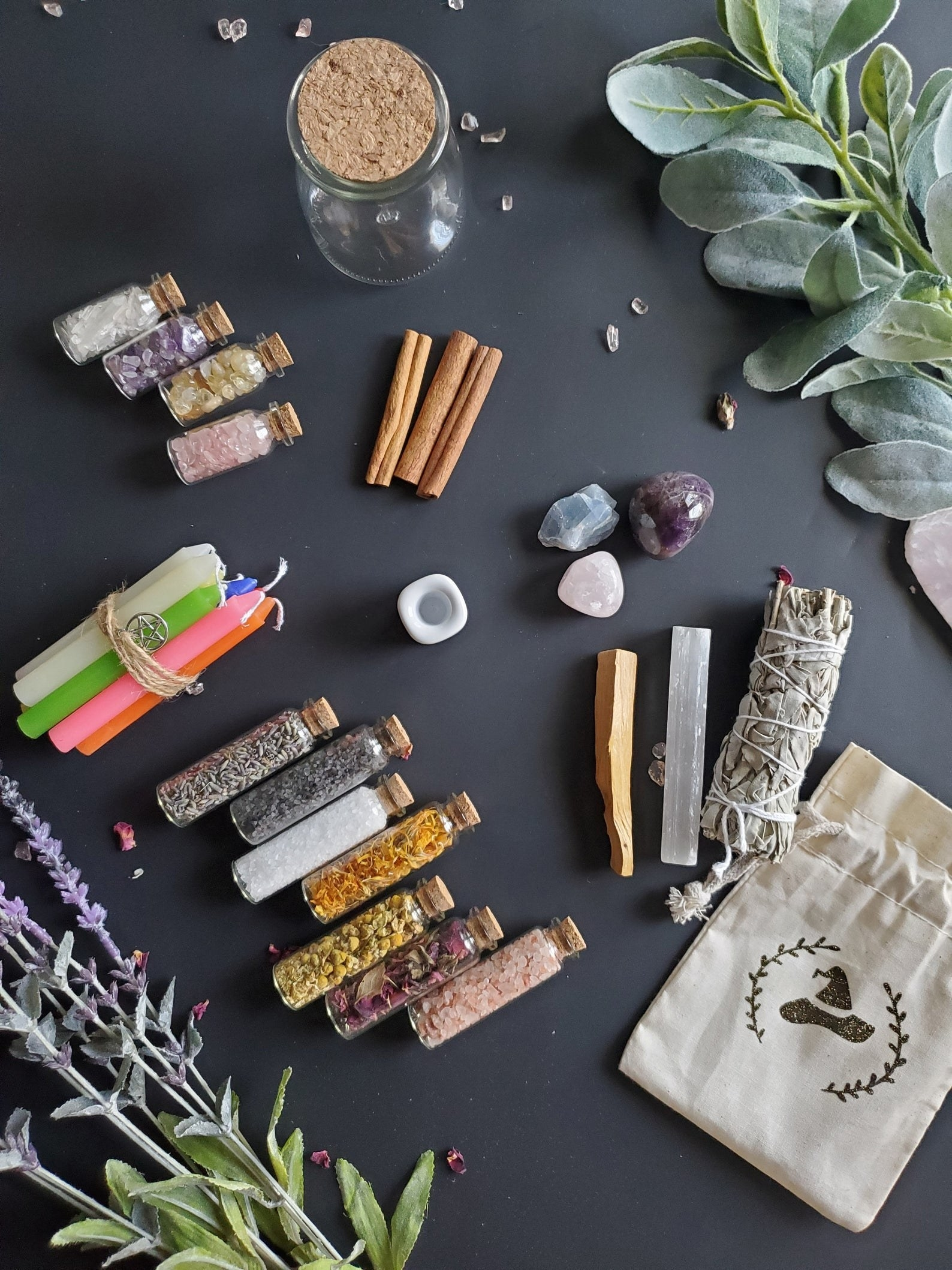 Some components of the kit including vials of verbs and crystals, stones, and candles