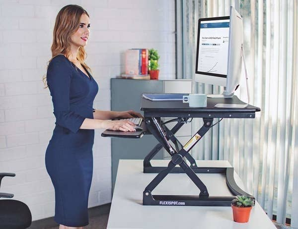 A person standing up and looking at their computer at eye-level with the standing desk on top of their desk