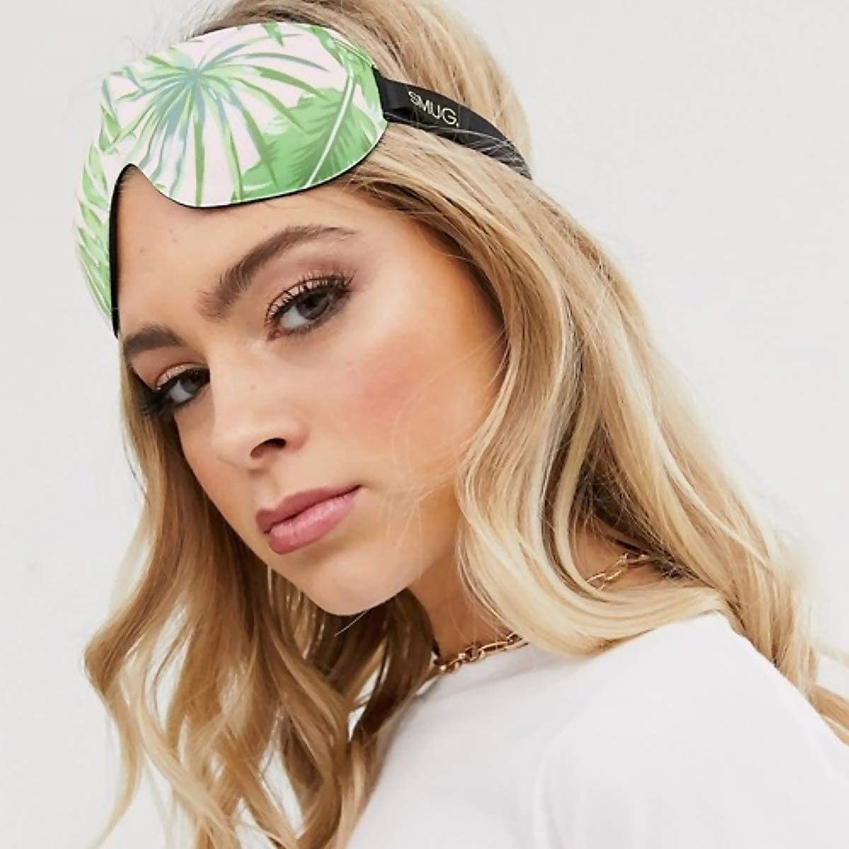 Green palm leaves on a contoured eye mask for sleeping