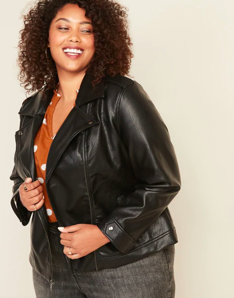 A person wears a faux leather jacket over a shirt and jeans