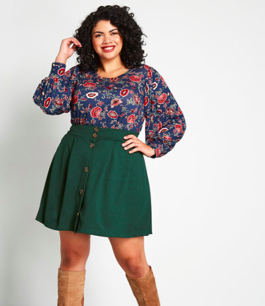 A person wears an above knee length skirt with buttons and a tucked in blouse