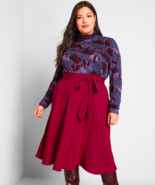 A person wears a swingy skirt with a tie at the waist and a tucked in turtleneck