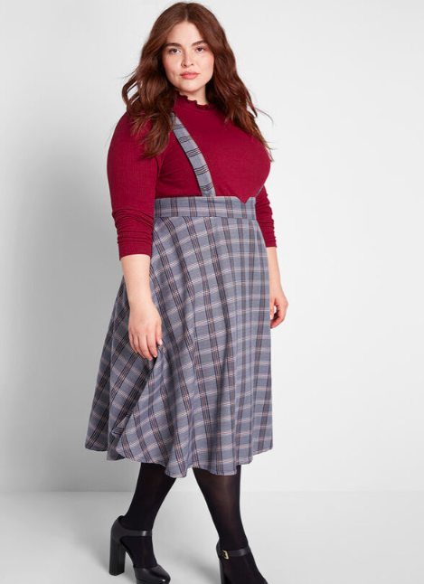 A person wears a skirt jumper with two straps and a blouse underneath
