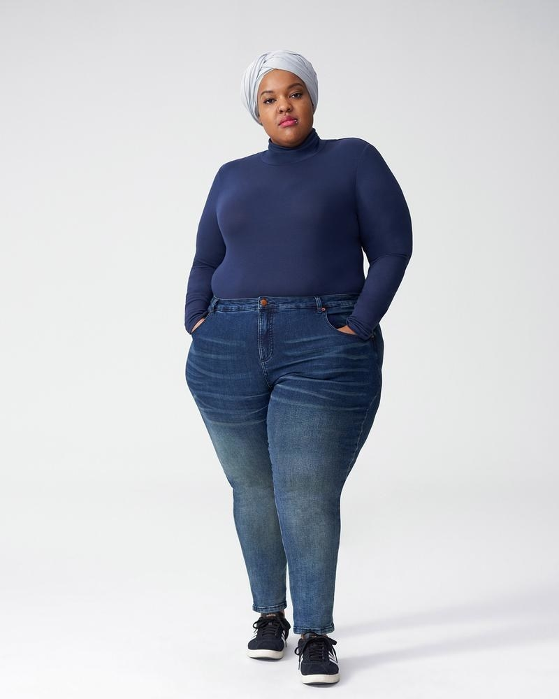 A person wears a turtleneck tucked into a pair of jeans