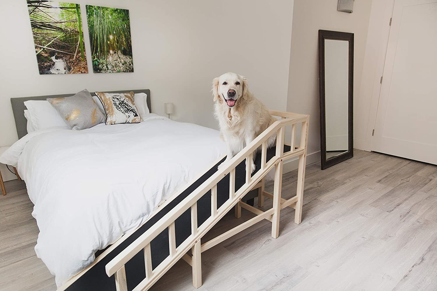 The ramp set up at the foot of a bed, with the rubber walkway slowly rising to bed height, with a railing on the far side of the ramp to prevent falls