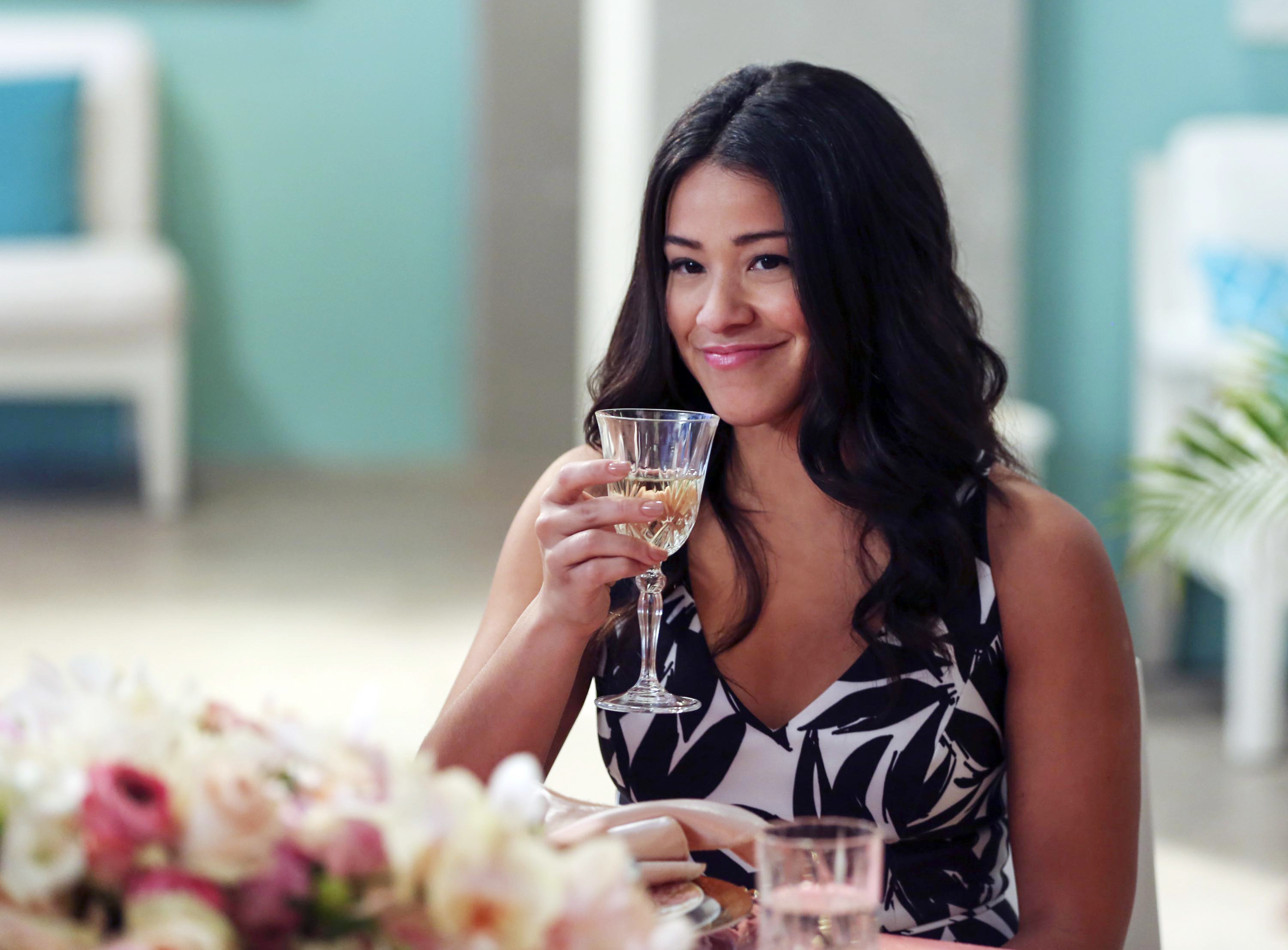 Jane grinning and hold up a glass