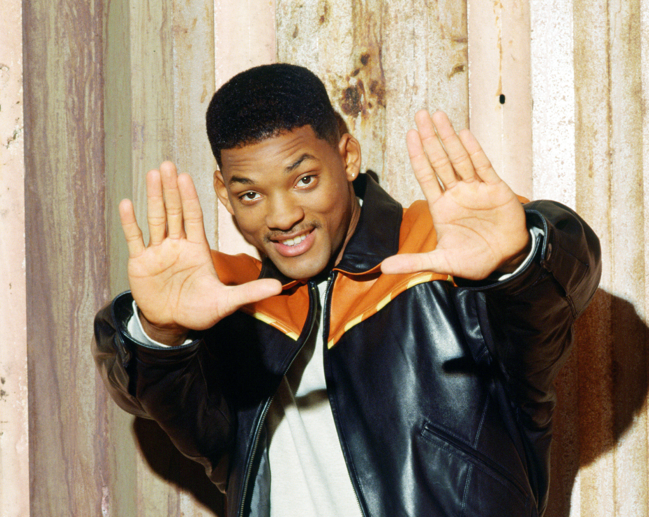 Will Smith smiling and holding his hands up