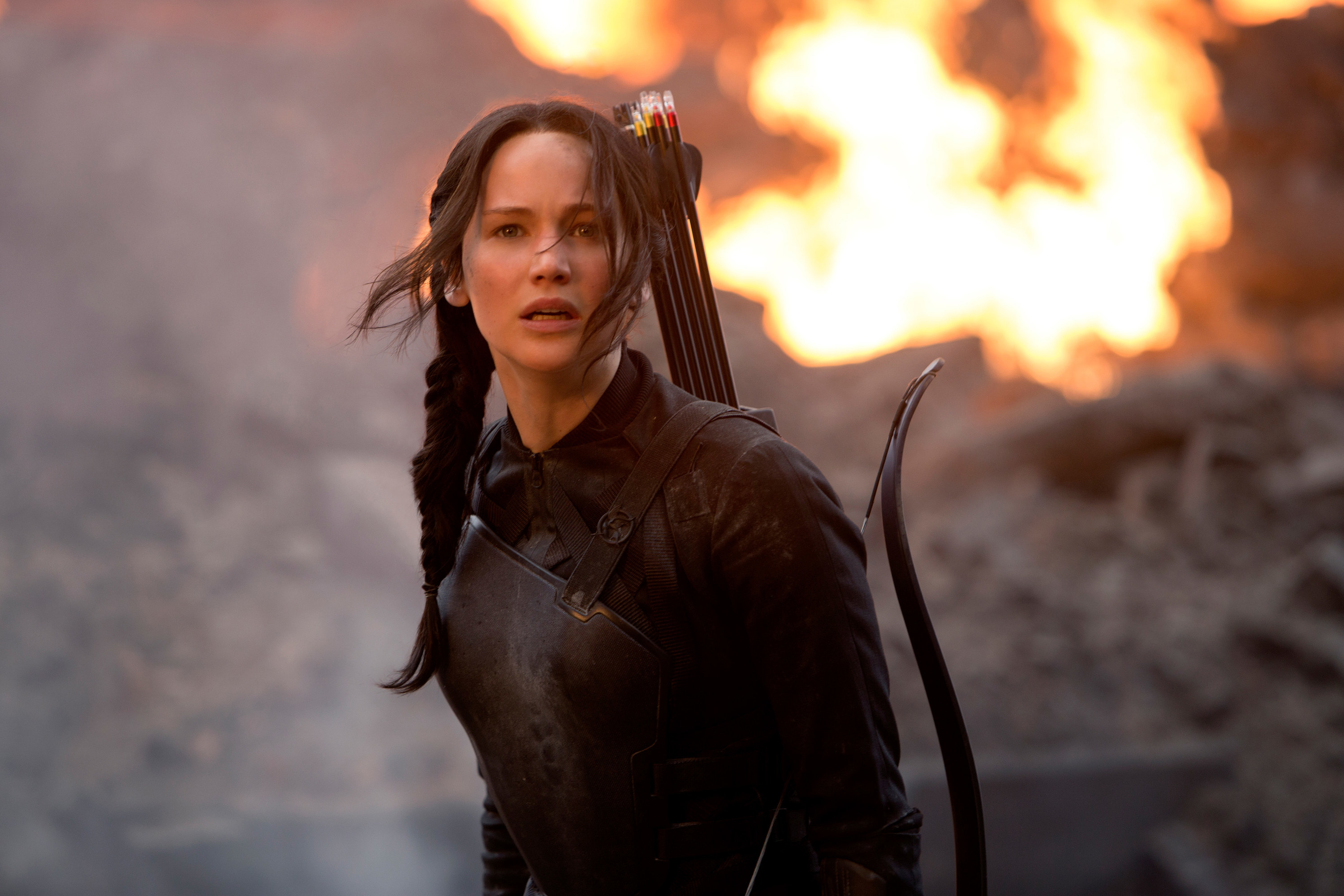 Katniss standing with an explosion behind her