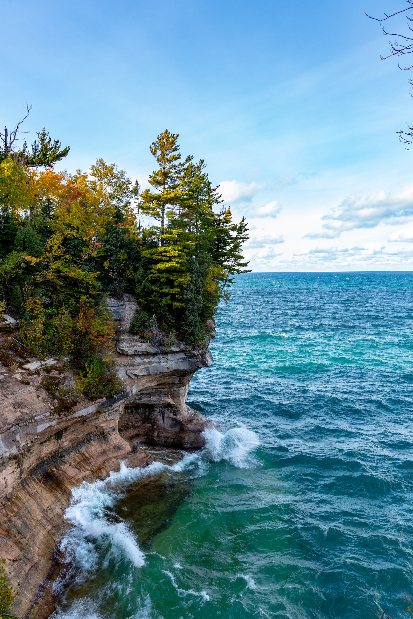 Cumulus clouds dot the horizon as Lake Superior's waves crash against a cliff face at Pictured Rocks National Lakeshore