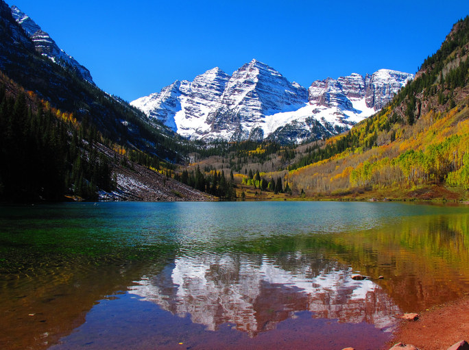 The iconic Maroon Bells mountain covered with snow is reflected in the mirror-like lake