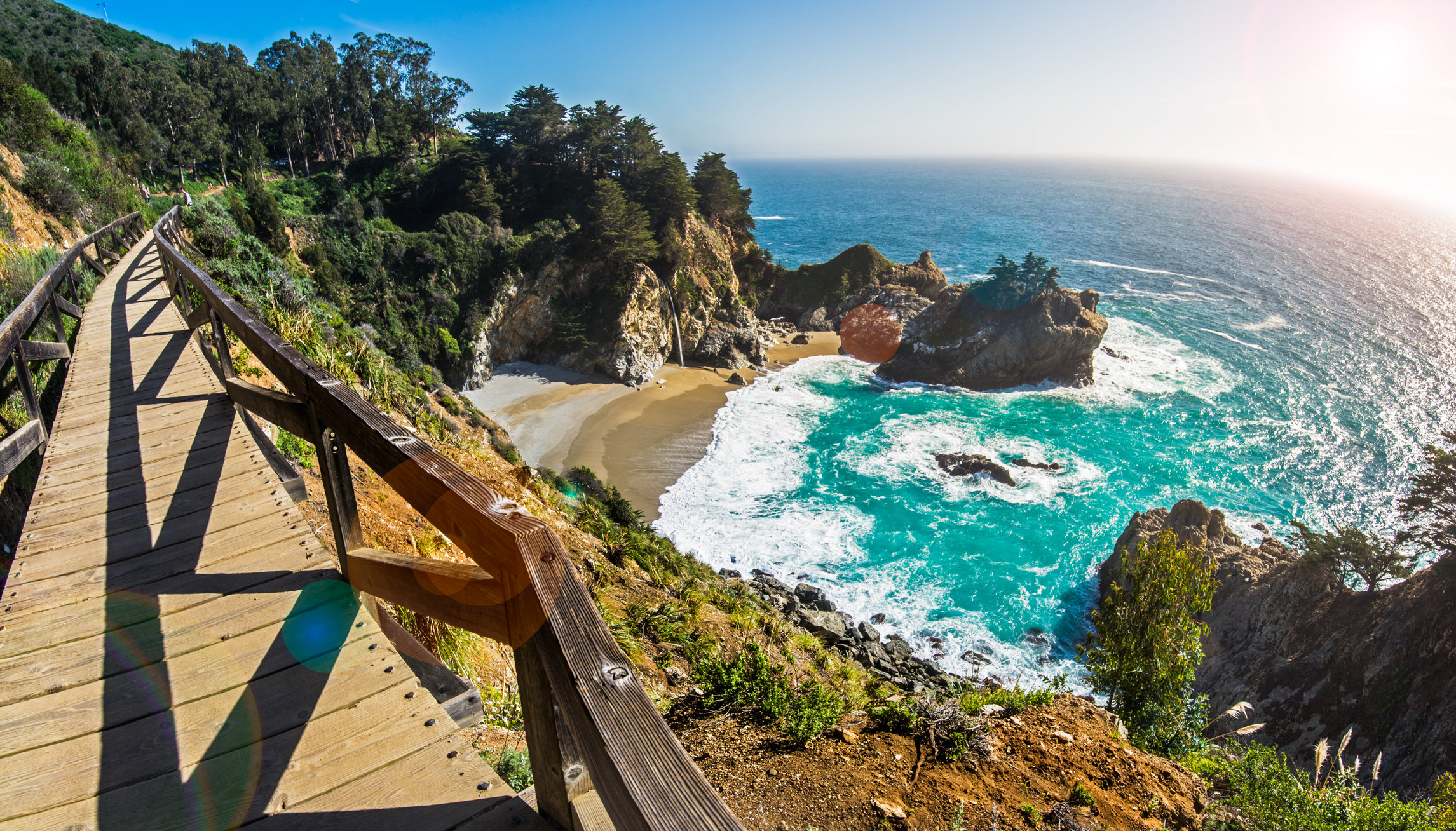A wooden footbridge winds around the cliff face overlooking McWay Falls at Julia Pfeiffer Burns State Park