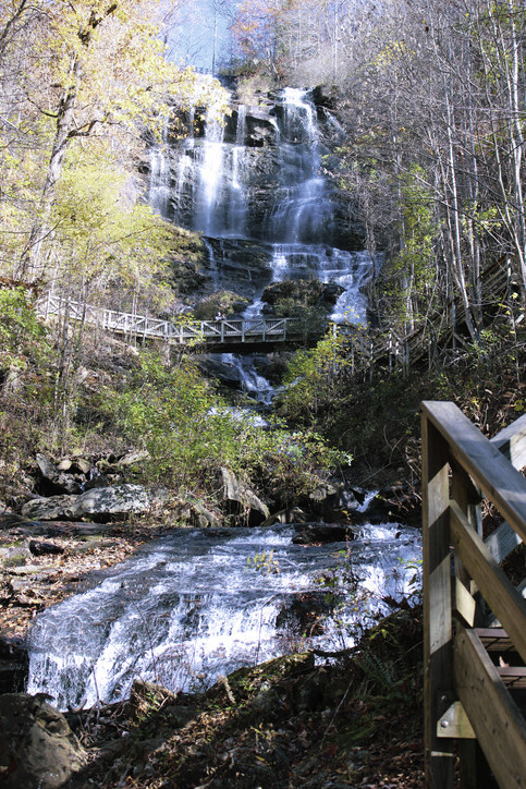 A footbridge winds around a towering. rocky waterfall