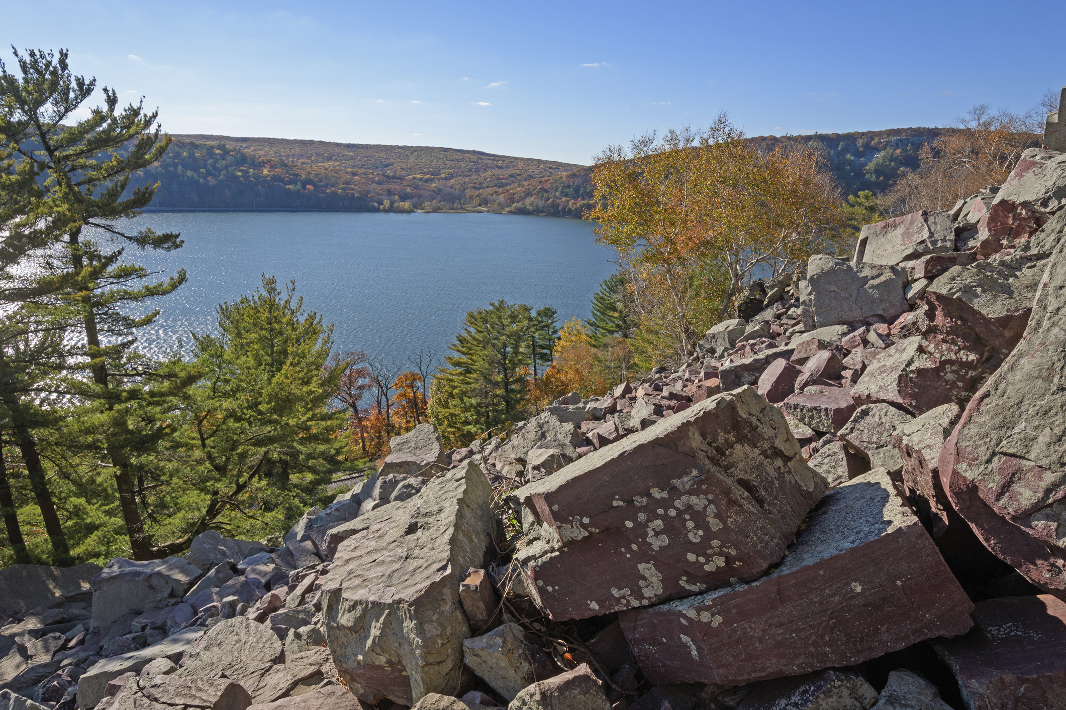 Fall-colored trees surround rocks and water at Devil's Lake State Park in Wisconsin